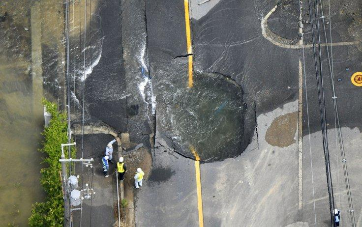 Water flows out from cracks in a road damaged by an earthquake in Takatsuki, Osaka prefecture, western Japan, in this photo taken by Kyodo June 18, 2018.