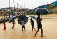 Rohingya refugee children walk along the water as parts of the Kutupalong camp flooded during heavy rain in Cox's Bazar, Bangladesh, July 4, 2018