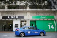 A ComfortDelgro taxi passes Uber and Grab offices in Singapore March 26, 2018.