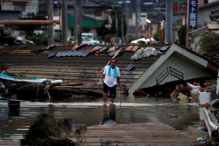 A local resident walks in front of submerged and destroyed houses in a flooded area in Mabi town in Kurashiki, Okayama Prefecture, Japan, July 8, 2018.
