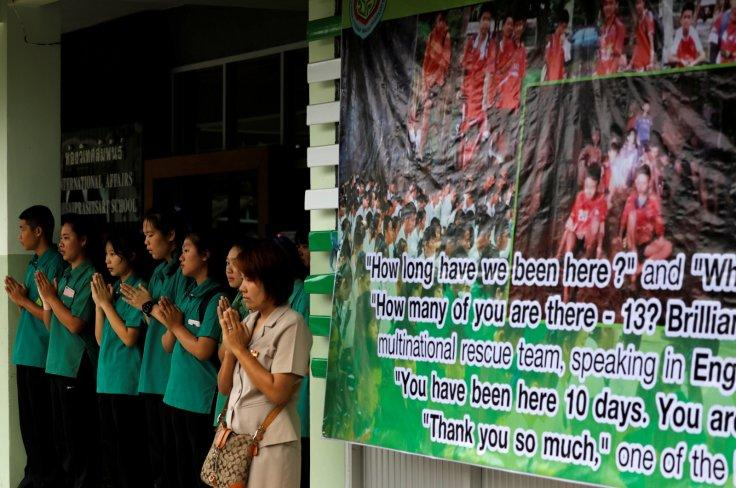 Schoolmates pray next to a banner showing 12 missing schoolboys, who were trapped inside a flooded cave, at Mae Sai Prasitsart school, in the northern province of Chiang Rai, Thailand, July 9, 2018.