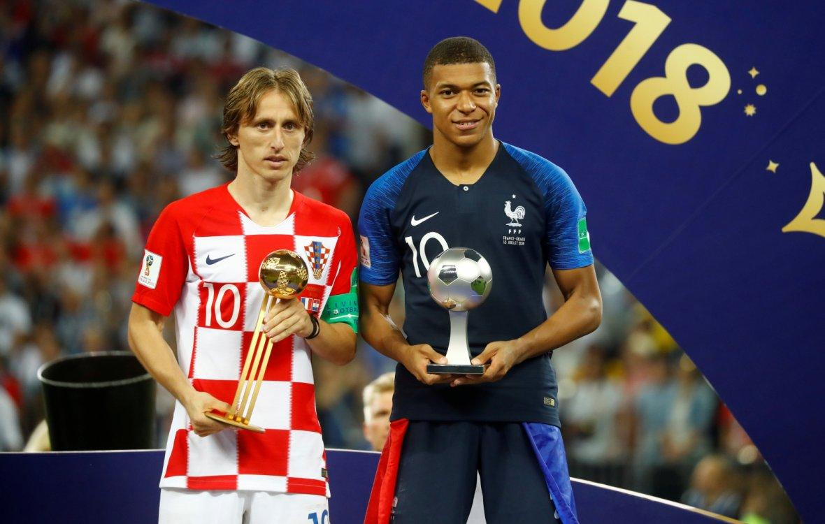 Croatia's Luka Modric poses with the FIFA Golden Ball award as France's Kylian Mbappe poses with the FIFA Young Player award