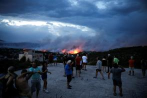People watch a wildfire raging in the town of Rafina, near Athens, Greece, July 23, 2018.