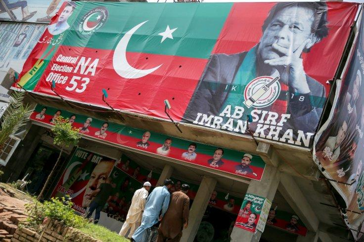 People walk past an image of cricket star-turned-politician Imran Khan, chairman of Pakistan Tehreek-e-Insaf (PTI) at a market in Islamabad, Pakistan, July 27, 2018.