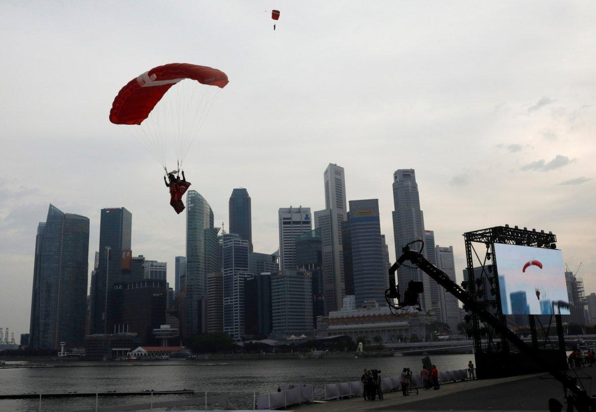 A Singapore Armed Forces Red Lions parachute team member performs at the National Day parade along Marina Bay in Singapore August 9, 2018.