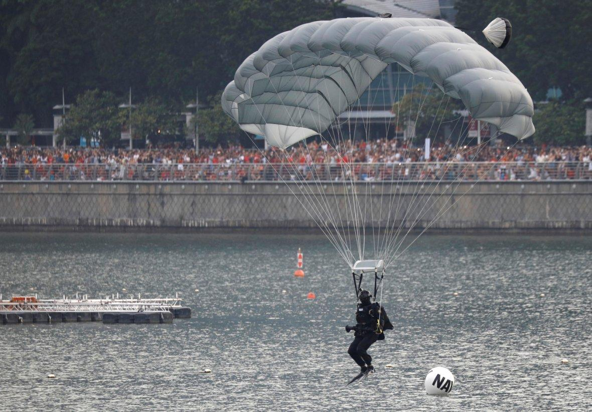 A Singapore Navy combat diver performs a water parachute landing at the National Day parade along Marina Bay in Singapore August 9, 2018.