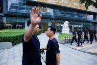 A police officer gestures at the photographer as security patrol outside the headquarters of China's banking regulator, to prevent planned protests by investors who lost money from collapsed peer-to-peer (P2P) online lending platforms, in Beijing, China