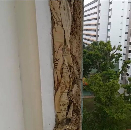 Screenshot of a video showing pieces of old newspaper stuffed in the walls of a balcony at an HDB flat.
