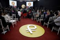 """The Venezuelan cryptocurrency """"Petro"""" logo is seen as Venezuela's President Nicolas Maduro speaks during a meeting with the ministers responsible for the economic sector at Miraflores Palace in Caracas, Venezuela March 22, 2018."""