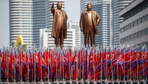 People carry flags in front of statues of North Korea founder Kim Il Sung (L) and late leader Kim Jong Il during a military parade marking the 105th birth anniversary Kim Il Sung, in Pyongyang April 15, 2017. REUTERS/Damir Sagolj/Files