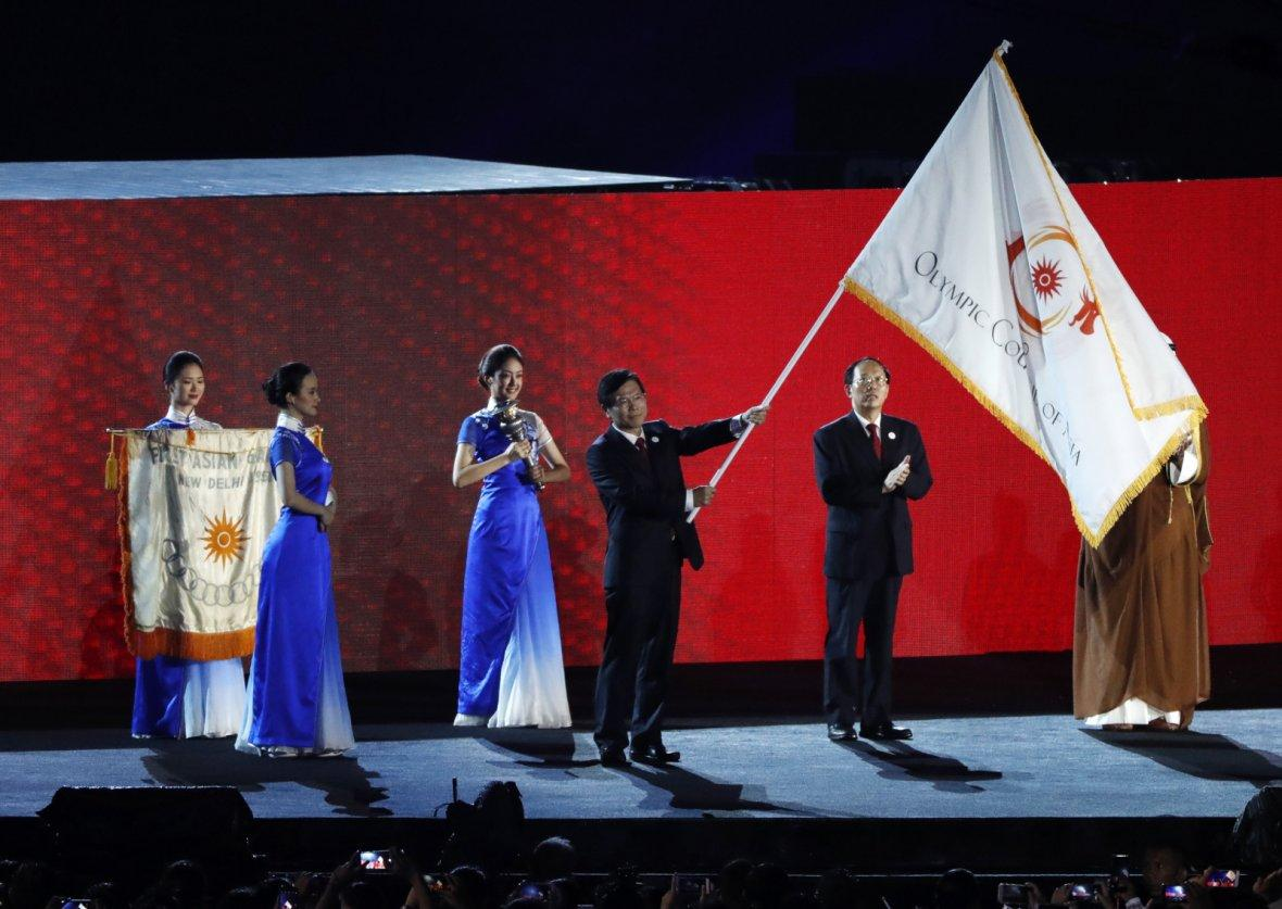 2018 Asian Games - Closing Ceremony - GBK Main Stadium - Jakarta, Indonesia - September 2, 2018 - A representative from China waves the Olympic Council of Asia flag after it was handed over by Indonesia.