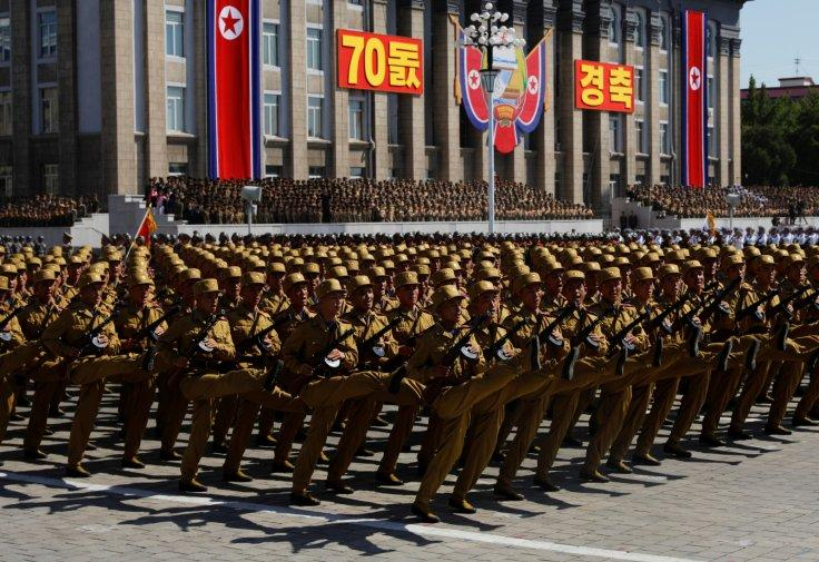 People wave plastic flowers and balloons during a military parade marking the 70th anniversary of North Korea's foundation in Pyongyang, North Korea, September 9, 2018.