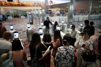 Passengers line-up at automated immigration control gates at Changi airport's Terminal 4 in Singapore April 30, 2018. Picture taken April 30, 2018. REUTERS/Thomas White
