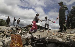 Residents walk on a collapsed mosque in Blang Mancung village after a 6.2 magnitude earthquake hit Aceh province July 3, 2013. Twenty seven people were killed and more than 200 were injured after the earthquake struck Aceh province on Tuesday, local media