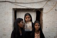 The daughters of Pakistani Christian woman Asia Bibi pose with an image of their mother outside their residence in Sheikhupura located in Pakistan's Punjab ProvinceReuters