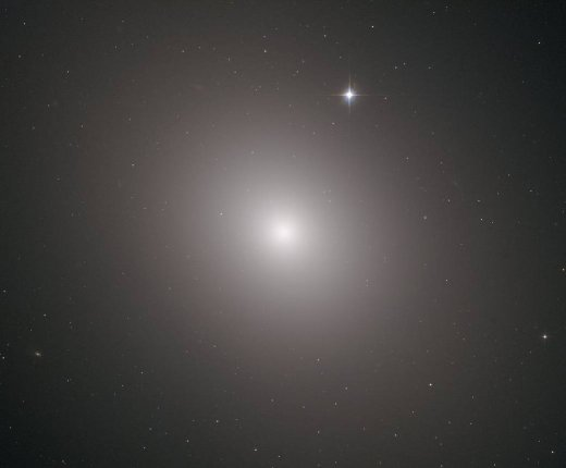 This fuzzy orb of light is a giant elliptical galaxy filled with an incredible 200 billion stars.