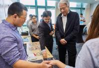 NUS Engineering Assoc Prof Jerald Yoo (second from right) demonstrating the Body Area Network project which aims to provide data and power connectivity through the human body to wearables, to Mr Teo