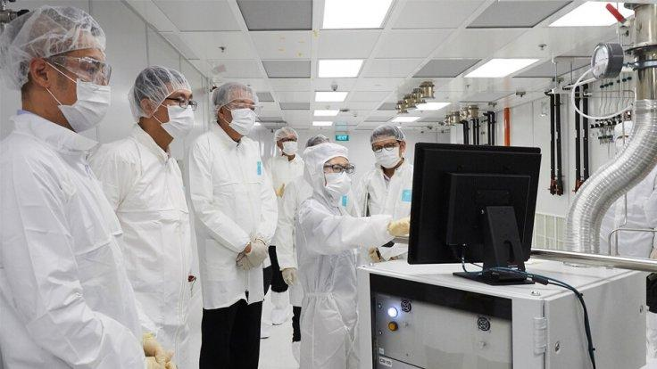 Mr Teo (third from left), together with Prof Tan (second from left) and Prof Chen (far left) in a cleanroom looking at data on a screen as a researcher explains how advanced atomic layer processing equipment works