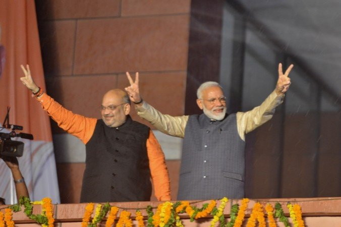 Prime Minister Narendra Modi and BJP chief Amit Shah wave at party workers during a party programme in New Delhi on May 23, 2019.