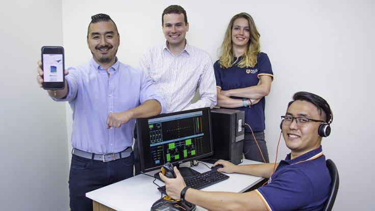 Prof Dean Ho (first from left) showing a schematic mobile version of CURATE.AI, while Mr Theodore Kee (seated) demonstrates the flight operations simulator software. With them are Asst Prof Christopher L. Asplund (second from left) and Dr Agata Blasiak (t