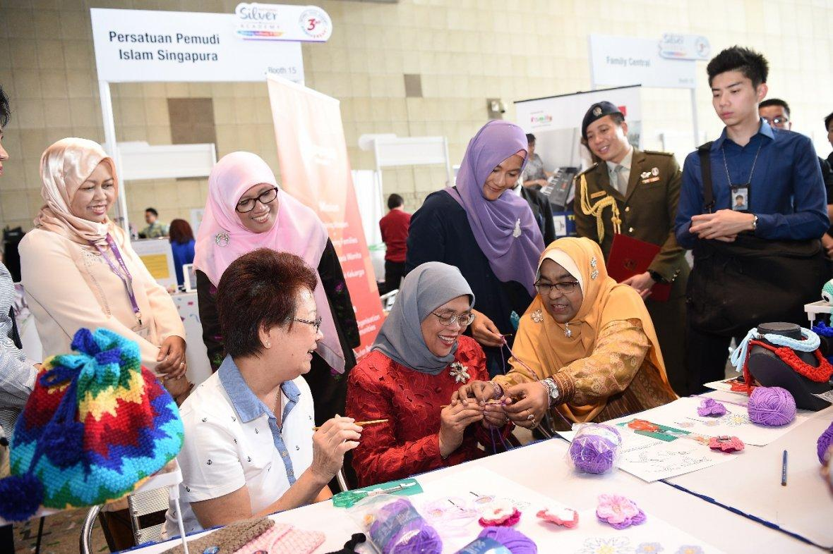 President Halimah Yacob took part in crochet-making with some seniors at the National Silver Academy's 3rd year anniversary roadshow.