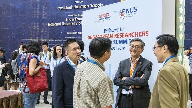Prof Tan (2nd from right) speaking with Singaporean researchers between events at the Summit