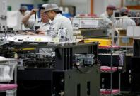 Employees are seen by their workstations at a printed circuit board assembly factory in Singapore