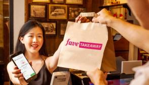 A satisfied customer picking up her Fave Takeaway order from a merchant