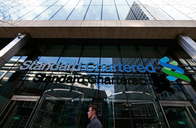 standard chartered bank posts losses