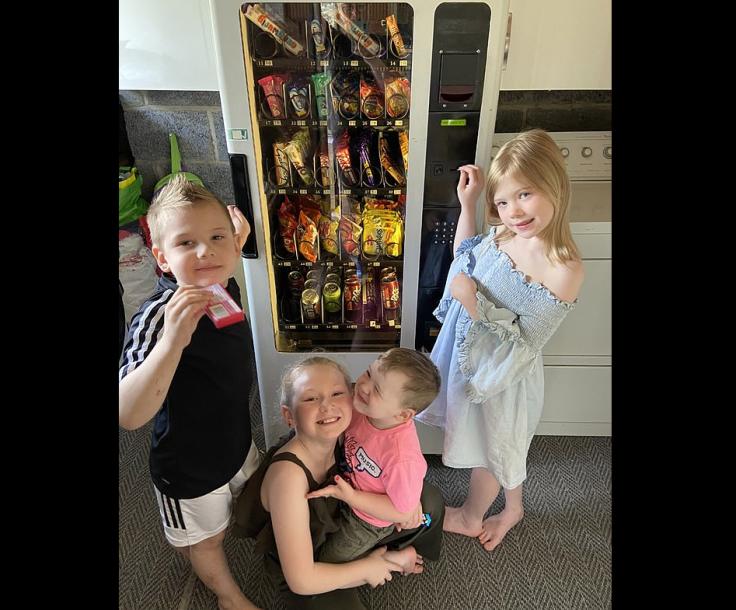 Kids get snacks from vending machine