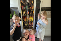 Kids get snacks from vending machine