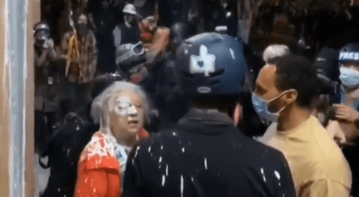 Protesters splash paint on Woman
