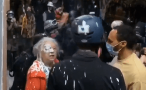 Protesters splash paint on Woman
