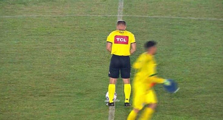 Referee peeing on ground