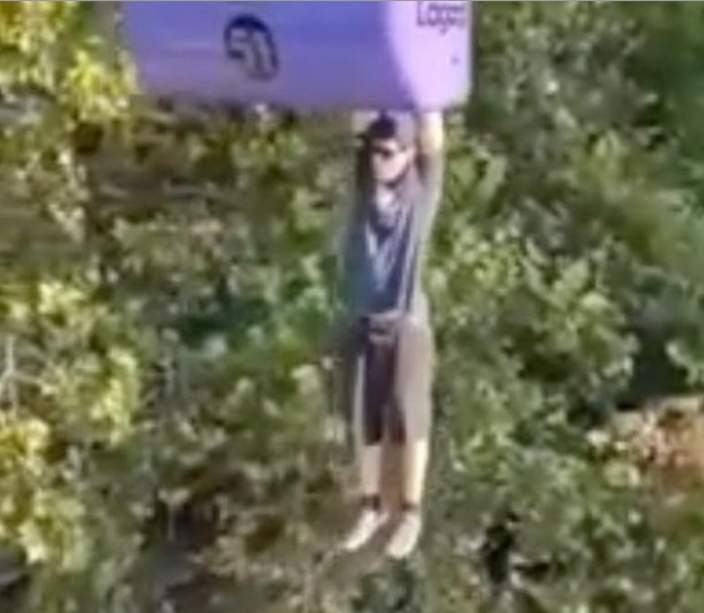 Man hanging form cable car