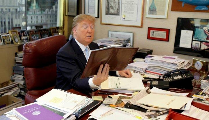 Donald Trump sifts through stacks of newspapers and printed articles to stay updated
