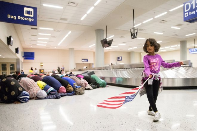 A young girl dances with an American flag